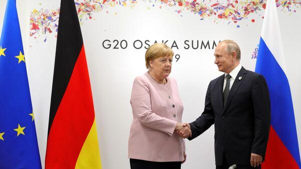 Президент РФ Владимир Путин и федеральный канцлер Германии Ангела Меркель во время встречи на полях Группы двадцати. 29 июня 2019