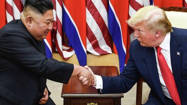 Лидер Северной Кореи Ким Чен Ын и президент США Дональд Трамп пожимают друг другу руки во время встречи на южной стороне военной демаркационной линии, которая разделяет Северную и Южную Корею. 30 июня 2019
