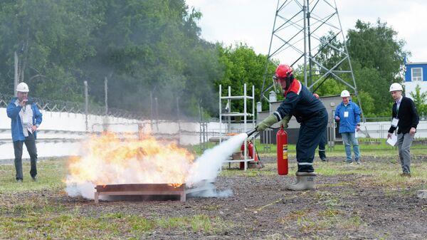 Сотрудник Россети Московский регион тушит пожар на соревнованиях энергетиков