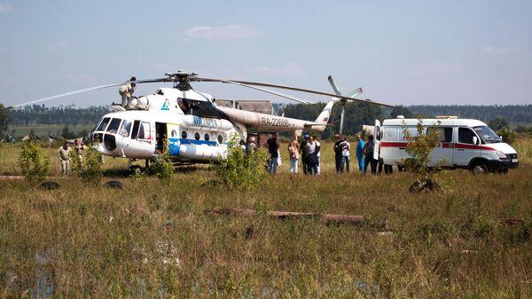 Вертолет Ми-8АМТ с медицинским модулем на борту и машина скорой помощи в Тулунском районе Иркутской области, где происходит ликвидация последствий паводка