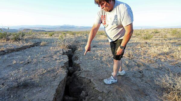 Мужчина смотрит на трещину в земле после мощного землетрясения в Калифорнии, недалеко от города Риджкрест