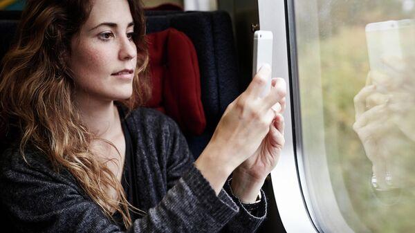 Девушка фотографирует из окна поезда