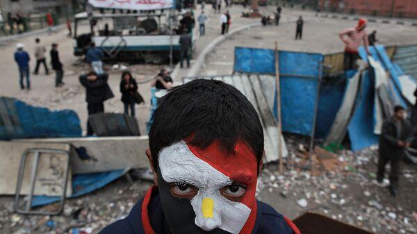 Сторонник оппозиции с лицом, раскрашенным в цвета государственного флага Египта, на баррикадах на площади Тахрир в Каире