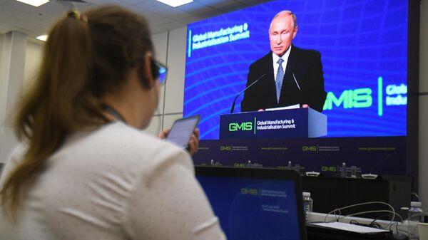 Журналист следит за выступлением президента РФ Владимира Путина на панельной дискуссии в рамках саммита GMIS-2019 в Екатеринбурге
