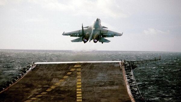 Палубный сверхзвуковой истребитель СУ-27К взлетает с палубы тяжелого авианесущего крейсера Северного флота Адмирал Кузнецов
