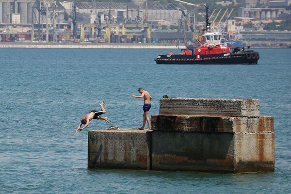 Молодые люди прыгают в море с пирса Новороссийска