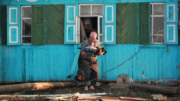 Местный житель возле разрушенного паводком дома в городе Тулун в Иркутской области