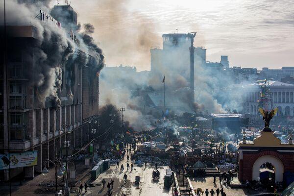 Дым от пожаров и сторонники оппозиции на площади Независимости в Киеве, где начались столкновения митингующих и сотрудников милиции