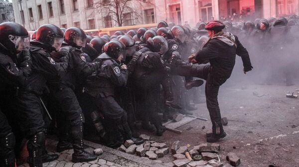 Участник акции сторонников евроинтеграции Украины перед строем сотрудников правоохранительных органов во время беспорядков возле здания Администрации президента Украины на Банковой улице в Киеве
