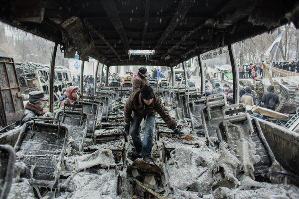 Сторонники евроинтеграции Украины у выгоревшей техники на улице Грушевского в Киеве