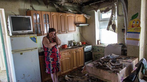 Женщина в своем доме, пострадавшем в результате ночного артобстрела со стороны украинских военных на окраине Славянска