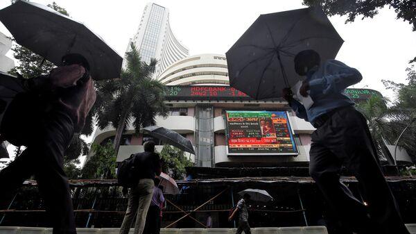 Люди проходят мимо здания фондовой биржи в Мумбаи, Индия