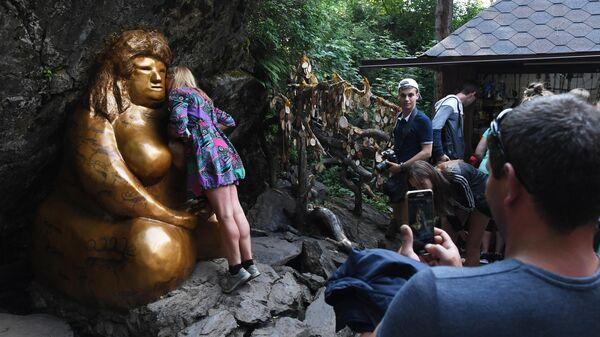 Отдыхающие возле статуи Золотая баба - достопримечательности всесезонного курорта Манжерок в Республике Алтай