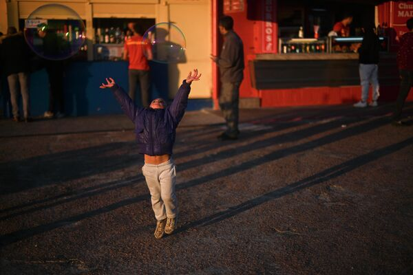 Девочка ловит мыльные пузыри в Монтевидео, Уругвай