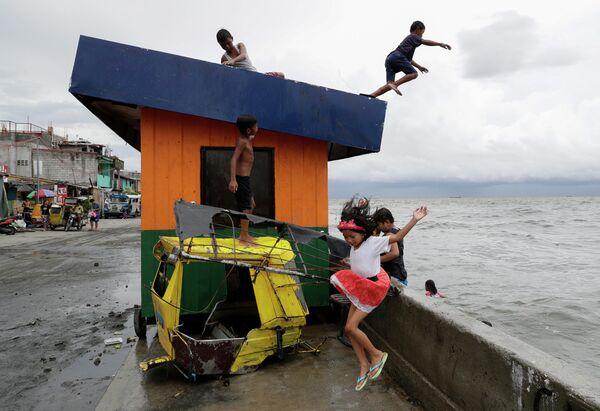 Дети прыгают в воду во время шторма на пляже в Маниле