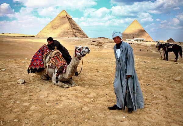 Местные жители стоят у пирамид в Гизе