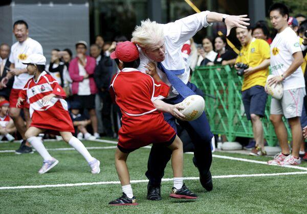 Мэр Лондона Борис Джонсон во время игры в регби с детьми в Токио. 15 октября 2015 года