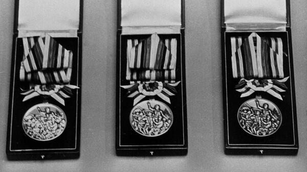 Медали XVIII Олимпиады в Токио - золотая, серебряная, бронзовая.