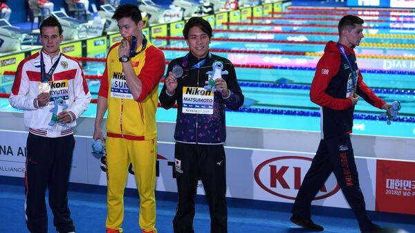 Британский пловец Данкан Скотт покидает церемонию награждения ЧМ по водным видам спорта в Кванджу в знак протеста против китайца Сунь Яна, замешанного в допинг-скандале.