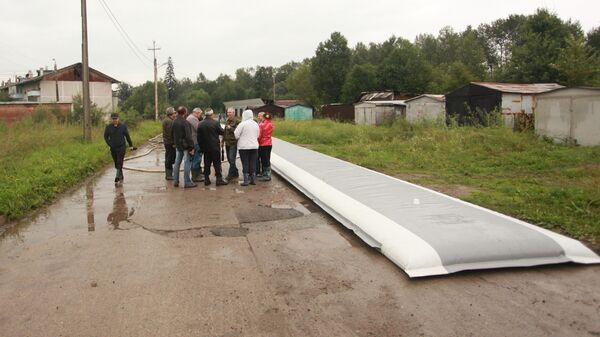 Сотрудники МЧС разворачивают водоналивную дамбу