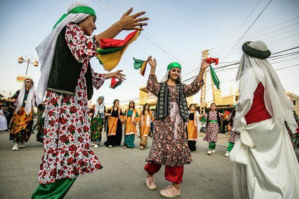 Сирийские курды в традиционной одежде танцуют на уличном фестивале в городе Румайлан