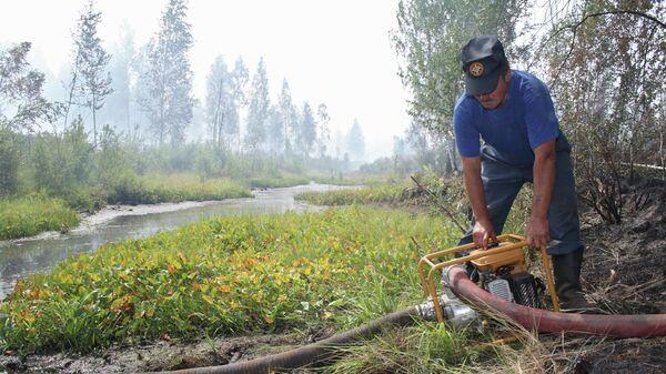 Участник тушения пожара с помощью мотопомпы закачивает воду из водоема