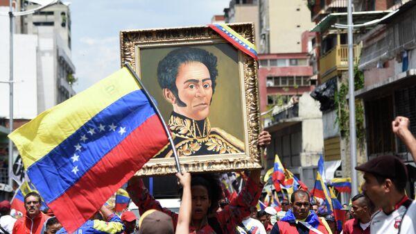 Участники акции протеста против санкционной политики США несут портрет Симона Боливара на одной из улиц Каракаса