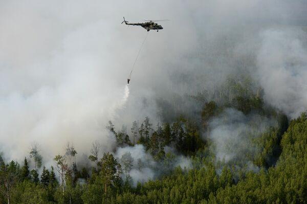 Вертолет Ми-8 с водосливной системой для забора воды в открытых водоемах во время тушения лесных пожаров в Богучанском районе Красноярского края