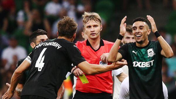 Сергей Лапочкин показывает желтую карточку Юнесу Намли (справа)