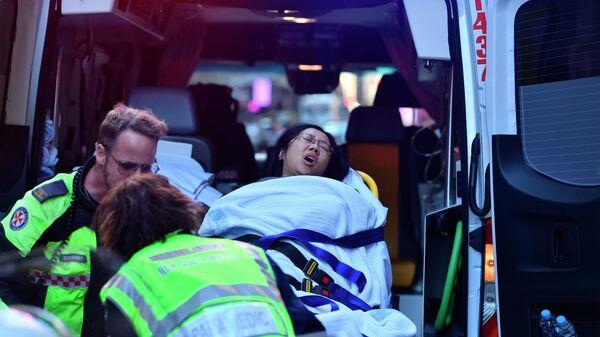 Машина скорой помощи забирает женщину из отеля CBD на углу улиц Кинг и Йорк в Сиднее, Австралия. 13 августа 2019