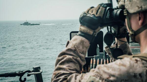 Морской пехотинец США наблюдает за иранским кораблем c американского военного корабля USS John P. Murtha  во время транзита через Ормузский пролив