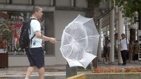 Мужчина во время дождя, вызванным тайфуном Кроса в Миядзаки