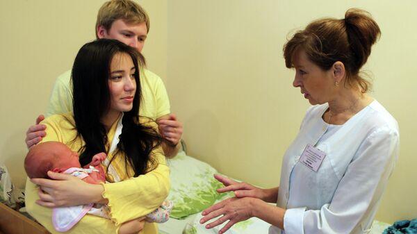 Молодые родители в одной из палат родильного отделения