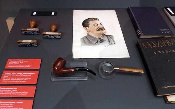 Факсимиле И. В. Сталина (1-я половина XX века), портрет И. В. Сталина, выполненный на шелке мастером Заборовской (1938 г.), трубка курительная (Великобритания, 1940-е гг.), лупа (1-я половина XX века), представленные на открытии историко-документальной выставки 1939 год. Начало Второй мировой войны