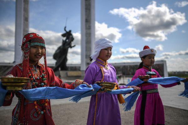 Девочки в национальных костюмах возле Мемориала, посвященного монгольским революционерам и героям войны, в городе Чойбалсан