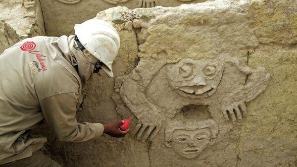 Специалист обрабатывает стену с избражением жабы  на археологических раскопках Вичама в районе Вегета, провинция Уаура, Перу