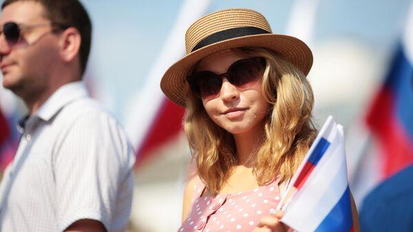 Девушка с флагом в рамках празднования Дня государственного флага Российской Федерации в центре Симферополя