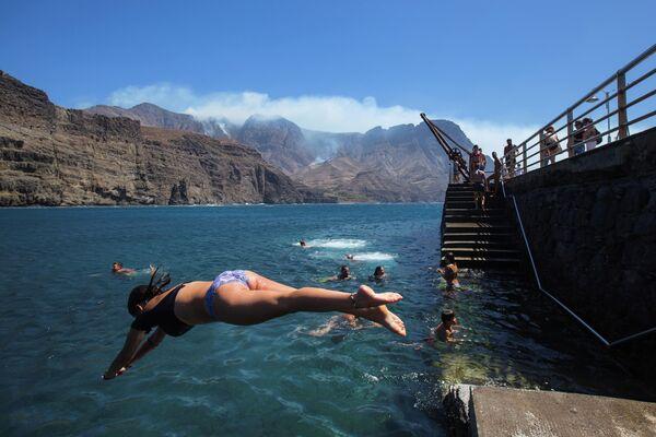 Люди купаются недалеко от очага лесного пожара на побережье Агаэте на острове Гран-Канария, Испания