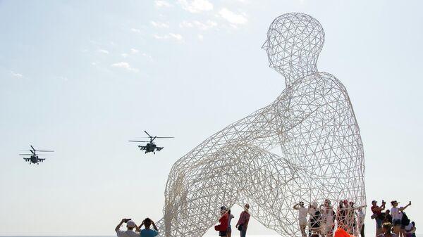 Зрители наблюдают за показательными выступлениями авиации в небе над площадкой фестиваля творческих сообществ Таврида - АРТ в бухте Капсель в Судаке