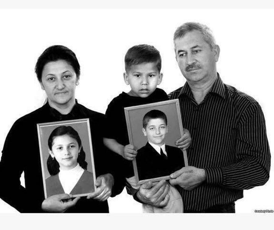 Эльвира Туаева вместе с мужем, маленьким Хетагом и фотографиями погибших детей