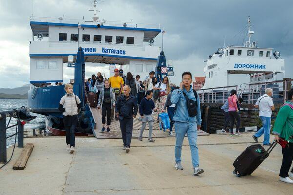 Иностранные туристы на паромной переправе острова Ольхон на озере Байкал в Иркутской области