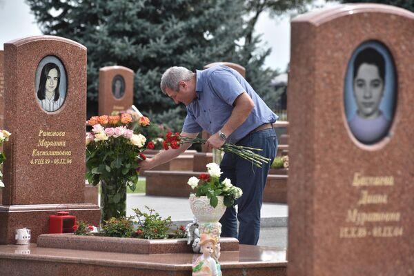 Мужчина принес цветы на могилу на мемориальном кладбище Город ангелов в Беслане, где похоронены погибшие во время теракта в 1-й Бесланской школе 1-3 сентября 2004 года