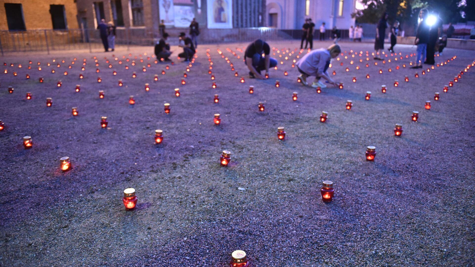 Жители зажигают свечи во дворе бывшей 1-й Бесланской школы в память погибших в теракте 1-3 сентября 2004 года - РИА Новости, 1920, 23.12.2020