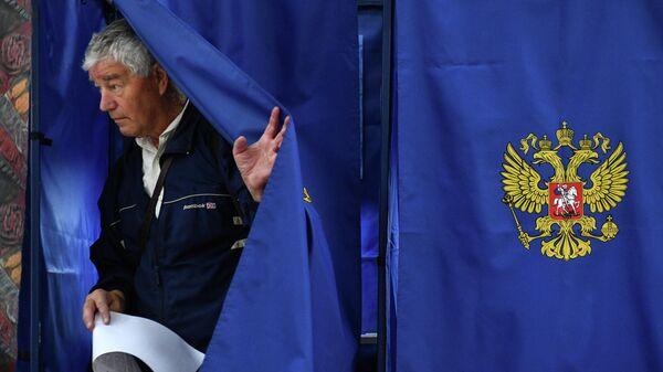 Мужчина голосует на выборах в единый день голосования на избирательном участке