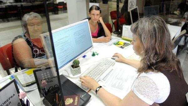 Сотрудник обслуживает посетителей в Центре государственных и муниципальных услуг