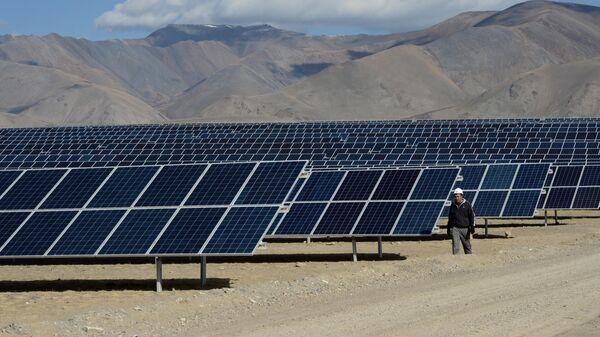 Мастер осматривает солнечные батареи на Кош-Агачской солнечной электростанции в Республике Алтай