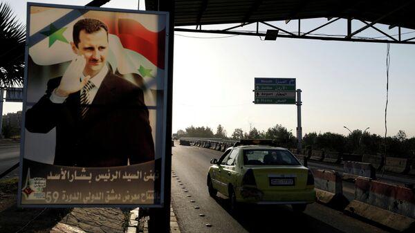 Плакат с портретом президента Сирии Башара Асада на дороге к аэропорту Дамаска