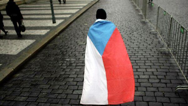 Мужчина с государственным флагом на улице Праги