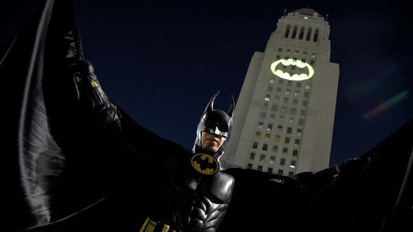 Мужчина позирует перед Bat-Signal, проецируемым на здание муниципалитета в Лос-Анджелесе