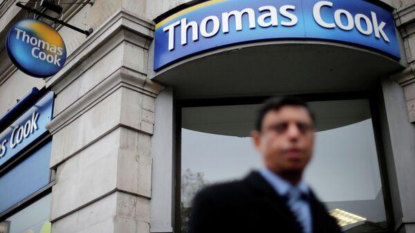 Прохожий у офиса туристической компании Thomas Cook в Лондоне